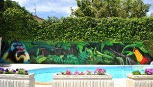 Rotulación a mano en Zaragoza - Mural exterior en casa particular: Selva junto a la piscina