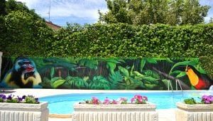 Rotulación a mano - Mural exterior en casa particular: Selva junto a la piscina
