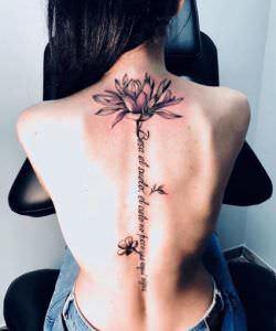 Tatuajes debajo del pecho mujer - Tatuaje espalda flor de lis en la columna con frase