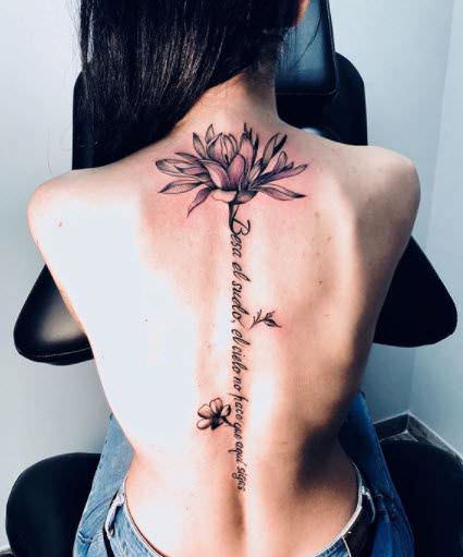 Tatuaje espalda flor de lis en la columna con frase