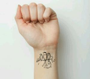 Tattoo con tres pájaros en la muñeca