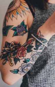 tattoo neotradicional de flores de colores en el brazo