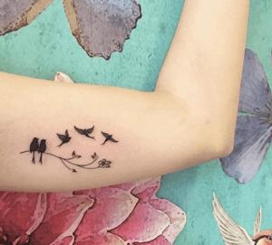 tattoo de golondrinas en una rama en el biceps brazo
