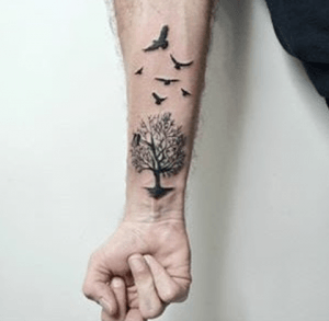 tattoo golondrinas volando junto a un árbol