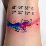 tattoo en la muñeca con coordenadas y elefante