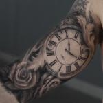 Tattoo de reloj grande en el brazo biceps
