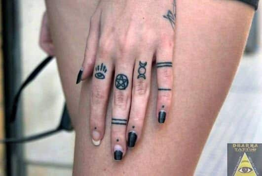Tatuajes símbolos en los dedos de una mujer