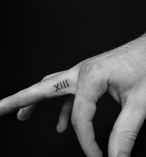 Tatuaje con número romanos en el dedo