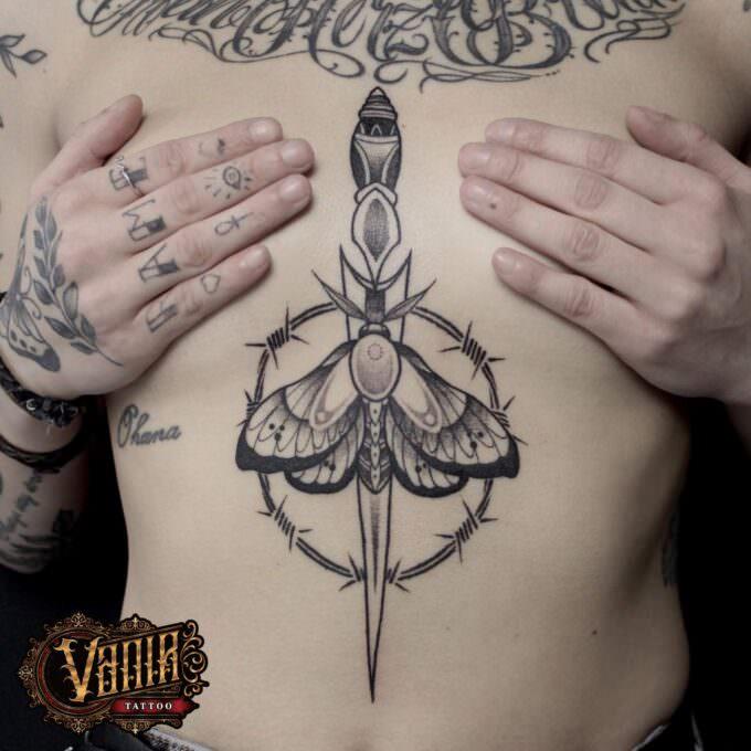 Tatuaje daga con mariposa entre el pecho