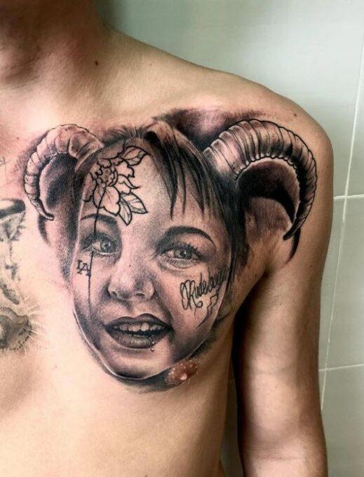 Tatuaje cara de una niña realista en el pectoral