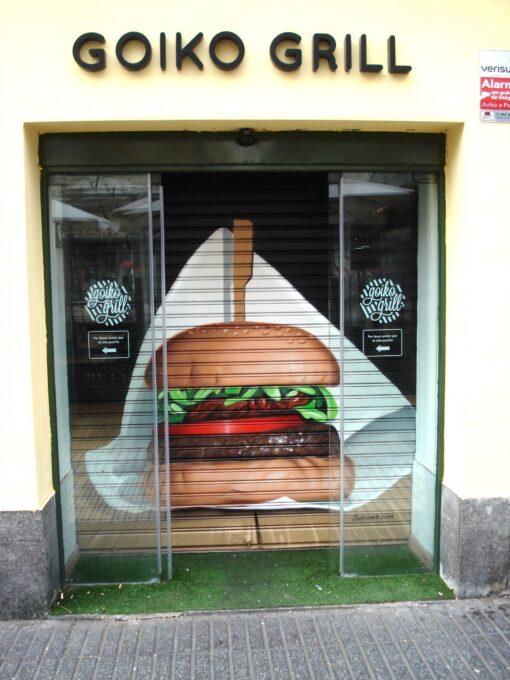 Graffiti en la persiana de la cadena de hamburgueserías Goiko Grill